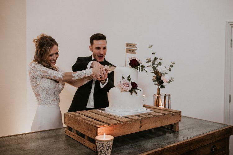Cutting The Wedding Cake | Bride in Madison James Bridal Gown | Groom in Tuxedo | Millbridge Court, Surrey Wedding with DIY Decor, Foliage & Giant Balloons | Nataly J Photography