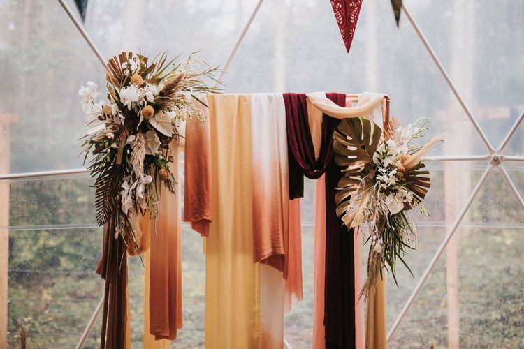 Wedding Altar Decor Covered in Drapes and Boho Flowers in Geometric Dome