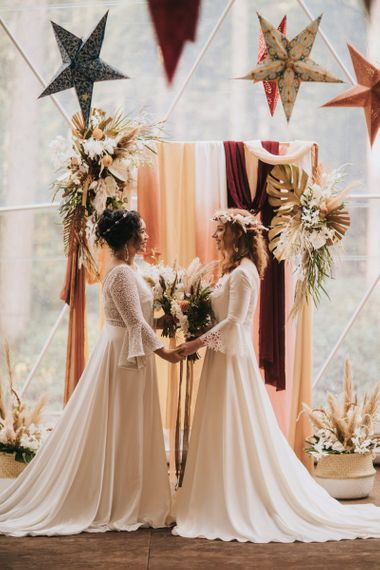 Boho Brides Standing at the Altar in Rolling In Roses Wedding Dresses in Geometric Dome