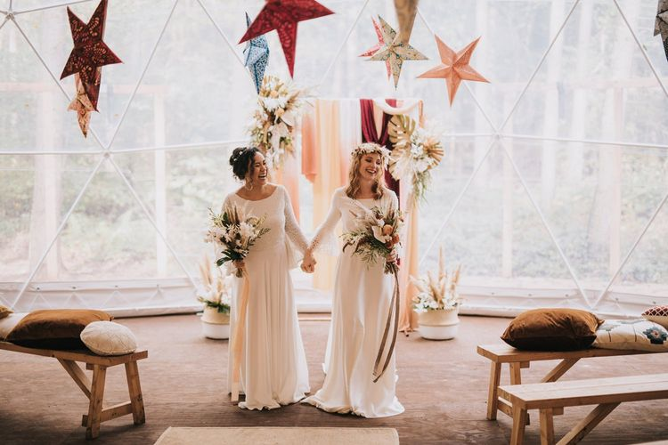 Bohemian Brides Walking Up the Aisle as Wife and Wide in a Geometric Dome