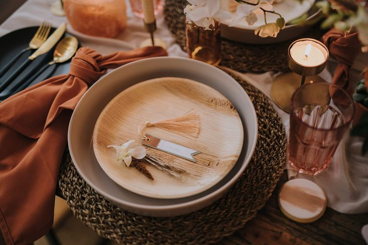 Place Setting with Terracotta and Wood Plates on Wicker Place Mats