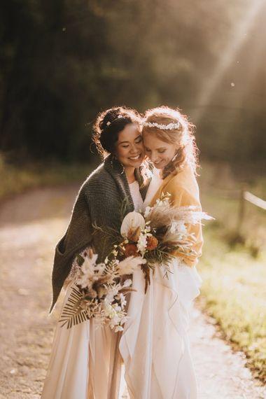 Same Sex Brides Embracing During Golden Hour