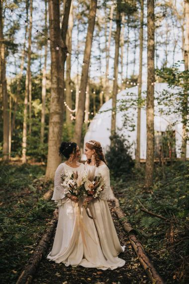 Boho Brides Standing in Camp Katur's woodland with the Geometric Dome Backdrop