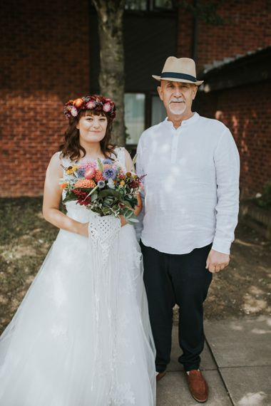 Father of the Bride and Daughter in Lace Wedding Dress with Bright Bouquet and Flower Crown