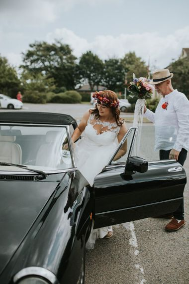 Bride in Lace Wedding Dress and Colourful Bridal Crown Getting into the Wedding Car
