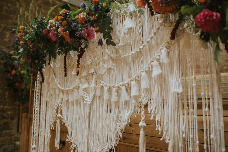 Homemade Macrame Wedding Backdrop with Bright Flower Decor