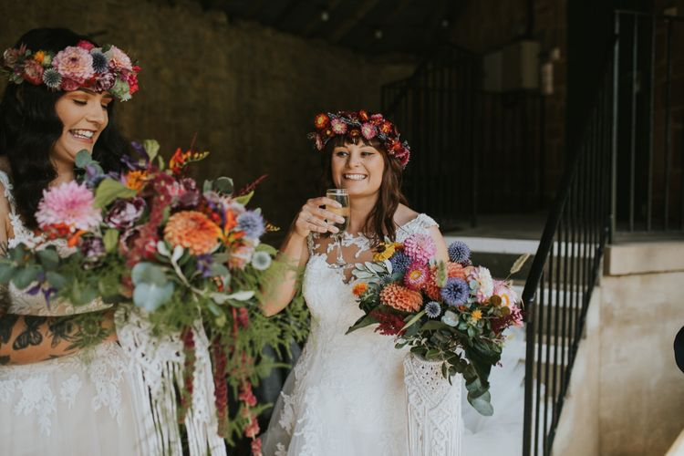 Two Brides in Lace Wedding Dresses with Colourful Flower Crowns and Bouquets at the Drinks Reception