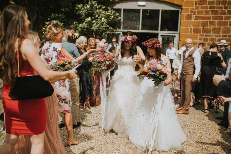 Confetti Moment with Two Brides in Lace Wedding Dress and Colourful Flower Crowns