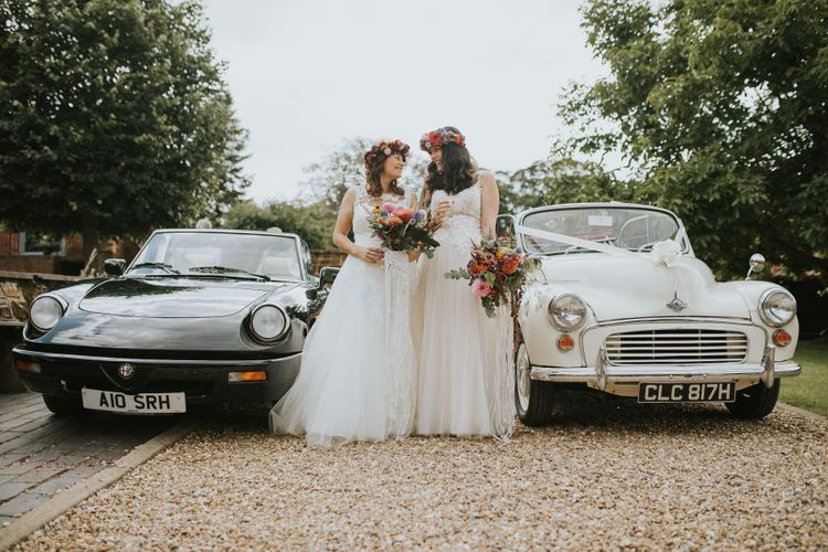 Two Brides in Lace Wedding Dress with Tulle Skirts Standing Next to Their Wedding Cars