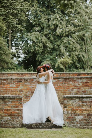 Two Brides in Lace Wedding Dresses Embracing