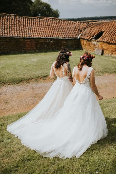 Two Brides in Lace Bow Back Wedding Dresses and Colourful Flower Crowns