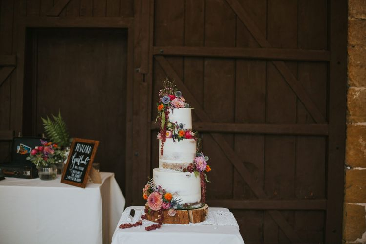 Semi Naked Wedding Cake on a Tree Slice Cake Stand Decorated with Wedding Flowers