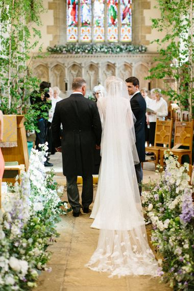 Lilac and white floral aisle runner   Silver Birch trees   Papakata Sperry Tent Wedding at family home   Sassi Holford Dress with added ivory Ostrich feathers to veil   Manolo Blahnik shoes   Images by Melissa Beattie