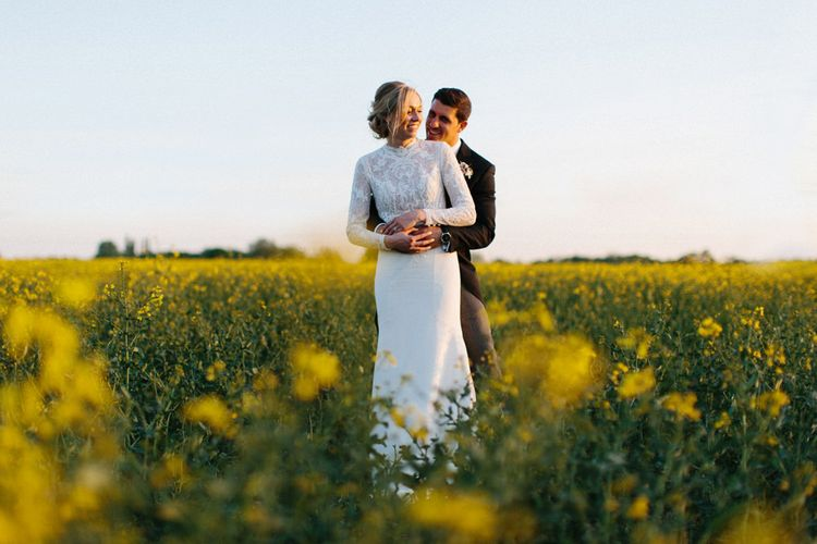 Yellow meadow couple shoot at dusk   Papakata Sperry Tent Wedding at family home   Sassi Holford Dress with added ivory Ostrich feathers to veil   Manolo Blahnik shoes   Images by Melissa Beattie