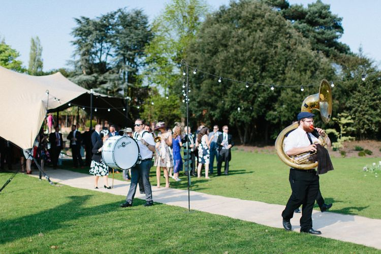 Roaming Band welcoming guests   Papakata Sperry Tent Wedding at family home   Sassi Holford Dress with added ivory Ostrich feathers to veil   Manolo Blahnik shoes   Images by Melissa Beattie