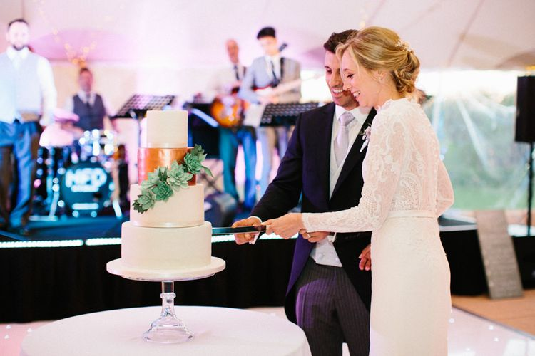 Simple elegant white cake with metallic layer and succulents   Papakata Sperry Tent Wedding at family home   Sassi Holford Dress with added ivory Ostrich feathers to veil   Manolo Blahnik shoes   Images by Melissa Beattie