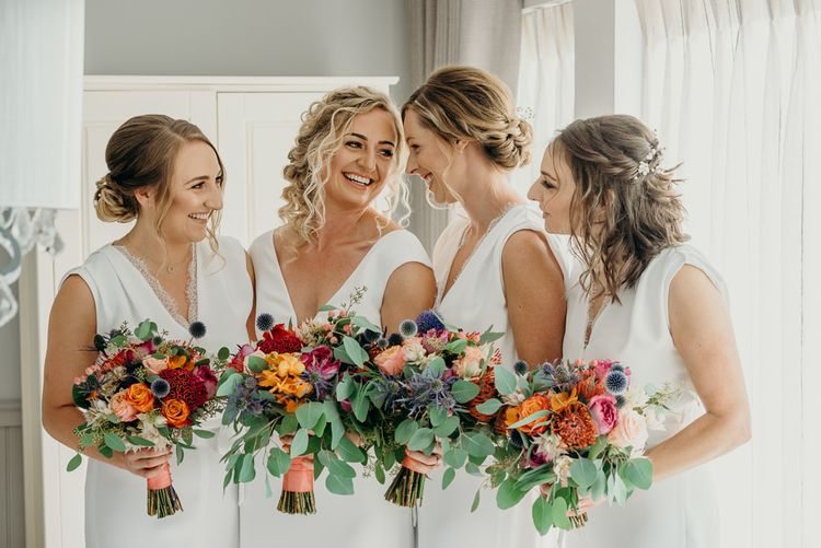 Bridesmaids in white jumpsuits with bright wedding flowers