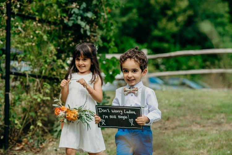 Cute kids at wedding with wedding sign