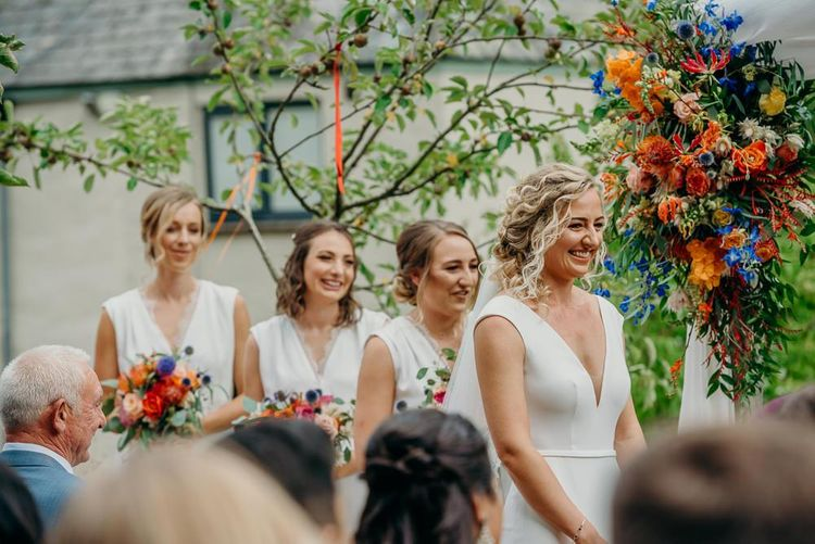 Bridal party at outdoor ceremony with bright wedding decorations