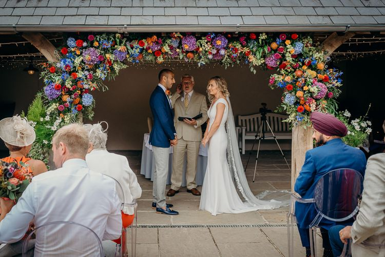 Outdoor ceremony with bright wedding decorations and stunning colourful flowers