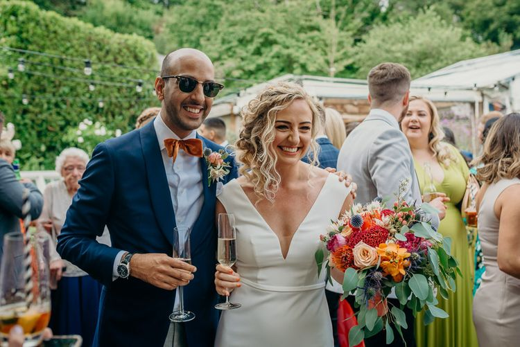 Bride and groom in blue wedding suit with bright bowtie