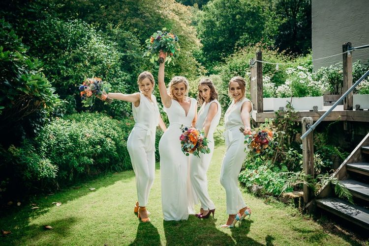 White jumpsuits for bridesmaids with bright wedding flowers