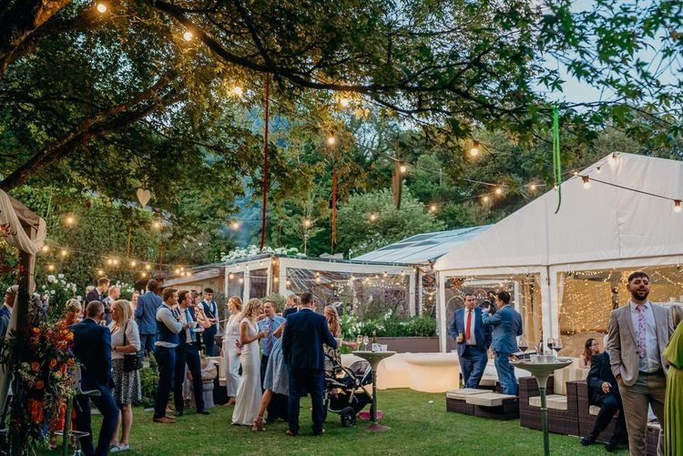 Wedding marquee with festoon lighting and bright wedding decorations