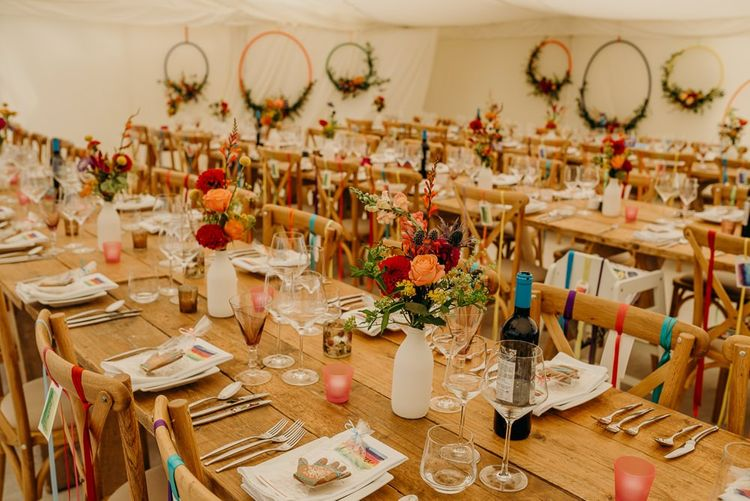 Bright wedding decorations and wooden banquet tables in marquee wedding