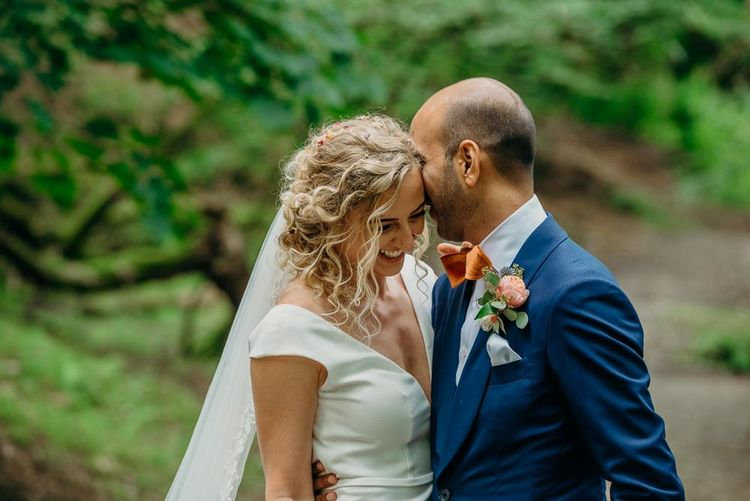 Curly haired bridal updo with simple wedding dress