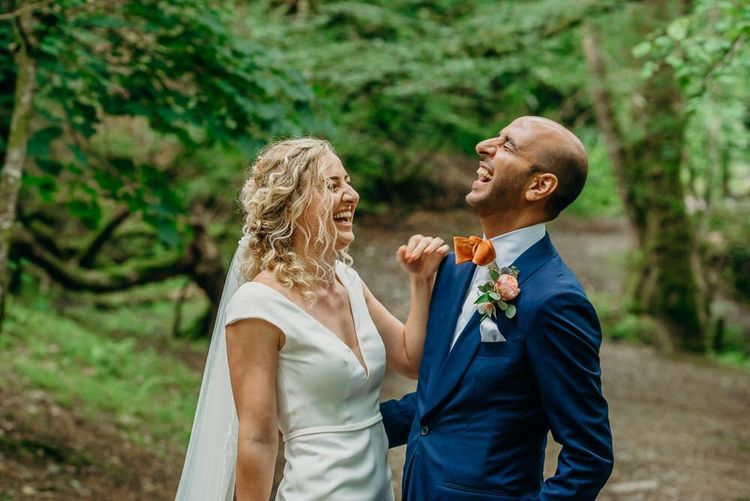 Groom wears blue wedding suit with bright bowtie