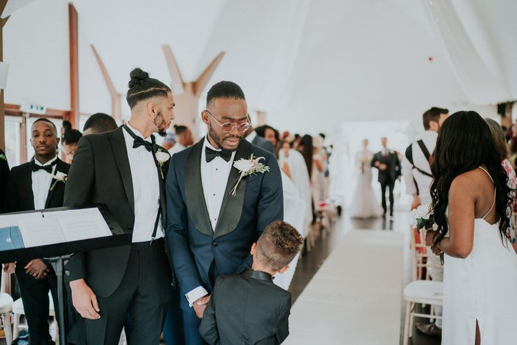 Groom in navy tuxedo and son at the altar waiting for the bride to enter