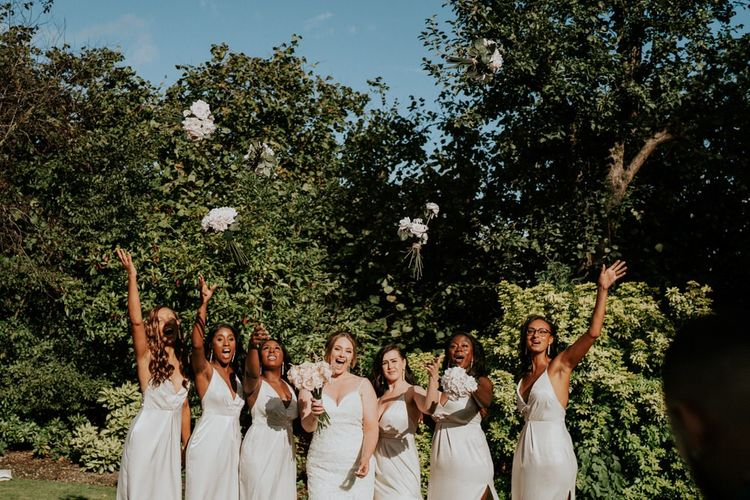 Bridesmaids in white dresses throwing their bouquets in the air