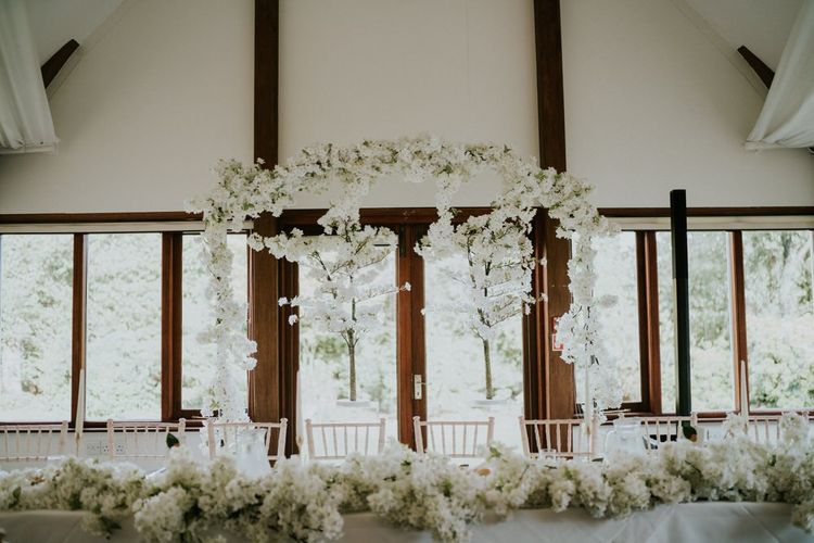 White blossom top table flowers and backdrop