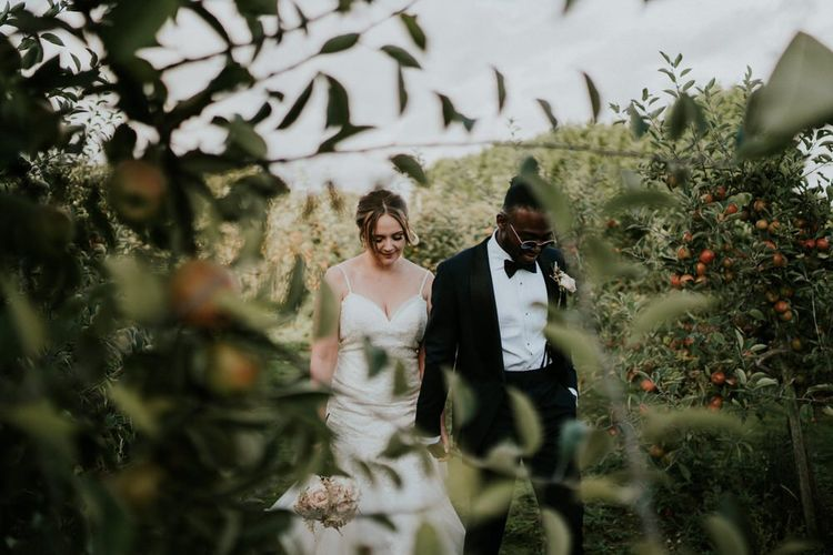 Bride and groom portrait in a field with bride in Morilee wedding dress