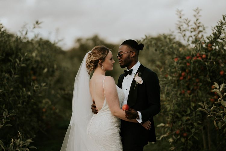 Bride and groom portrait in an orchard with bride in Morilee wedding dress