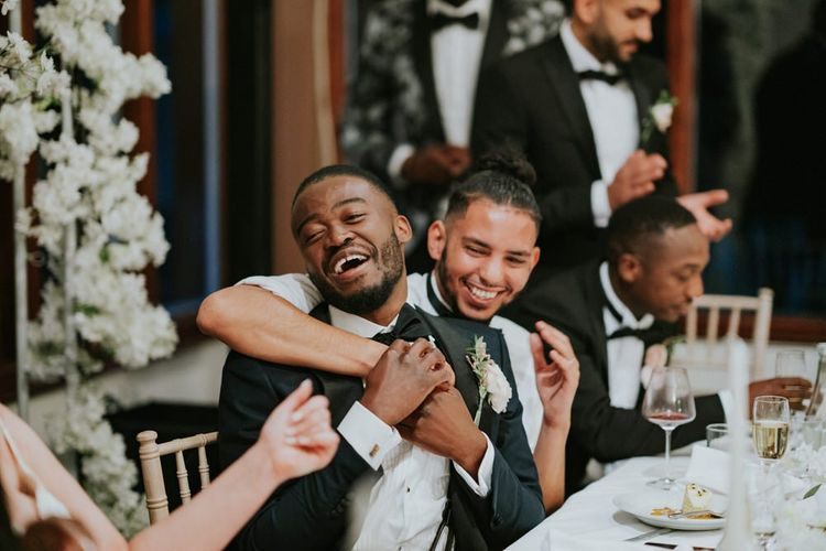 Groom and best man hugging at wedding reception