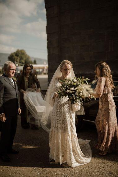 Bride in Bell sleeve wedding dress makes her way to wedding ceremony