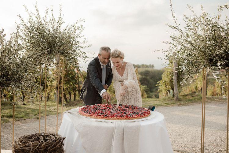 Bell sleeve wedding dress with groom cutting wedding cake