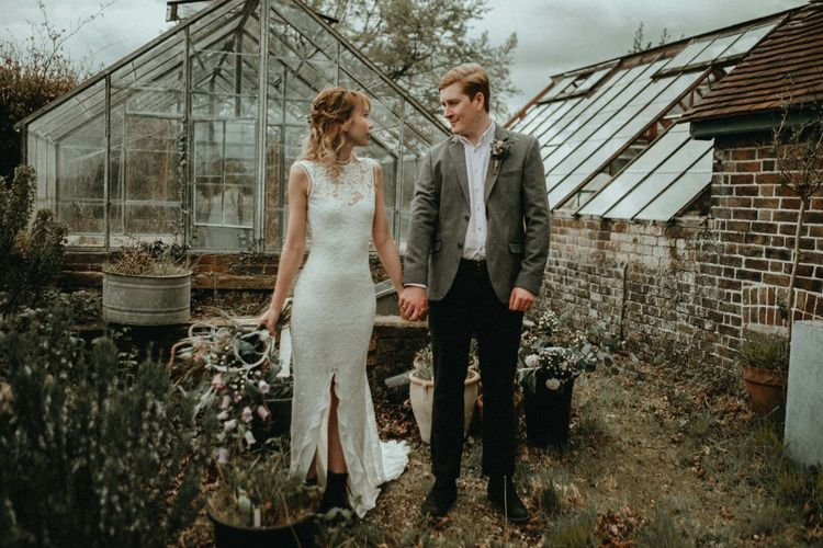 Bride in Lace Wedding Dress with Front Split and Groom in Wool Blazer Holding Hands by a Greenhouse