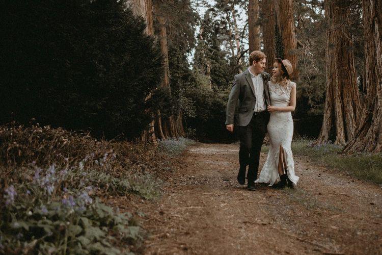 Bride in Lace Wedding Dress and Felt Hat and Groom in Wool Blazer Walking Through The Woodlands