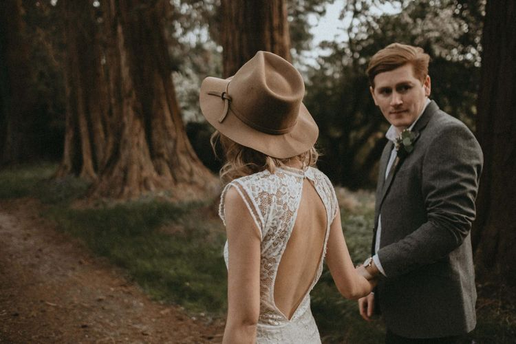 Bride in Backless Lace Wedding Dress and Felt Hat and Groom in Wool Blazer Holding Hands Walking Through The Woods