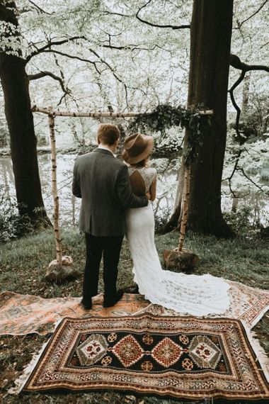 Boho Bride in Lace Wedding Dress and Felt Hat and Groom in Wool Blazer  Standing in Front of Wooden Frame and Rug Altar