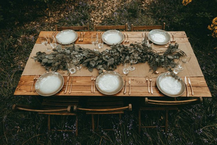 Wooden Table with Greenery Runner and Gold Cutlery