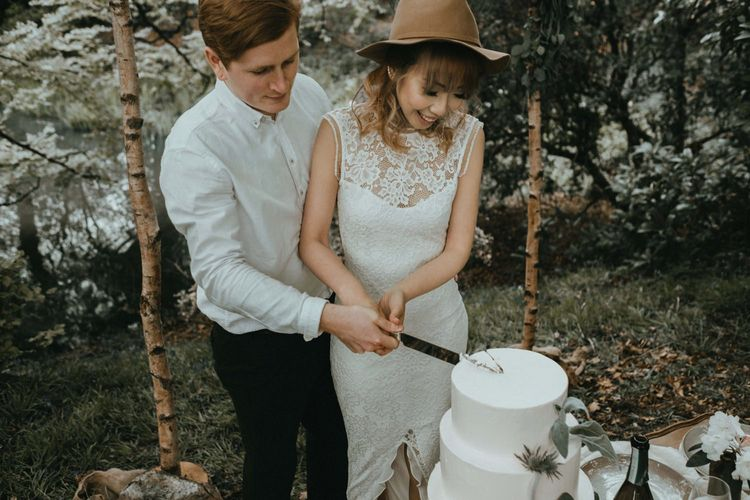 Boho Bride in Lace Wedding Dress and Felt Hat Cutting the White Buttercream Wedding Cake