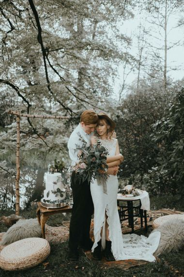 Groom Embracing His Boho Bride in Lace Wedding Dress with Front Split, Boots and Felt Hat