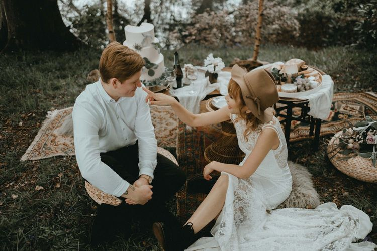 Boho Bride in Lace Wedding Dress and Felt Hat and Groom in White Shirt Enjoying Their Grazing Table