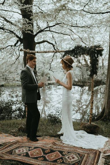 Boho Bride in Lace Wedding Dress and Felt Hat and Groom in Wool Blazer   Exchanging Their  Wedding Vows