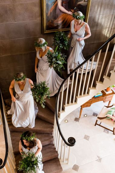 Bridesmaids in grey dresses walking down the stairs