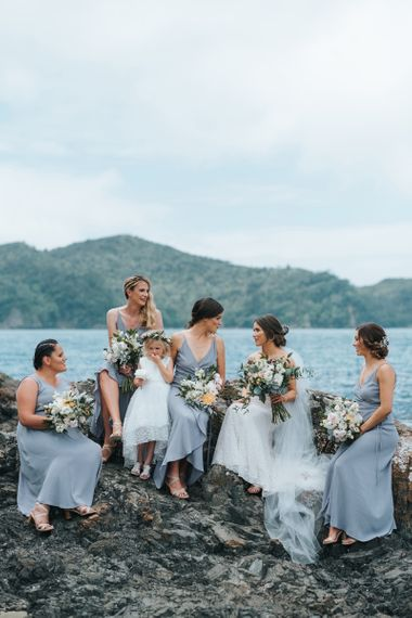 Bridal party sitting on a rock by the sea in grey bridesmaid dresses