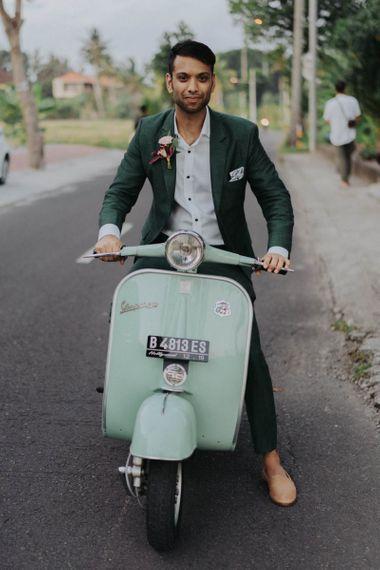 Groom in Dark Green Coloured Suit on a Vespa Motorcycle